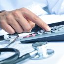 nito500150500007.jpg - closeup of a young caucasian healthcare professional wearing a white coat calculates on an electronic calculator