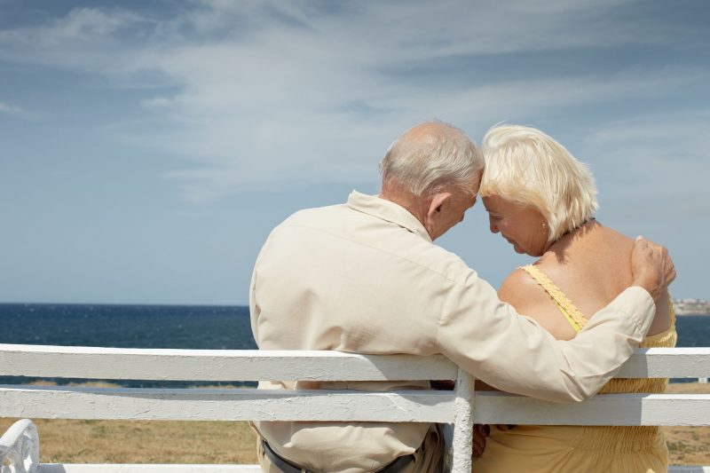 diego - senior caucasian couple sitting on bench near the sea and hugging. horizontal shape, rear view, copy space