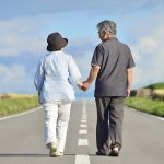 paylessimages150116672.jpg - senior couple walking a single road holding hands