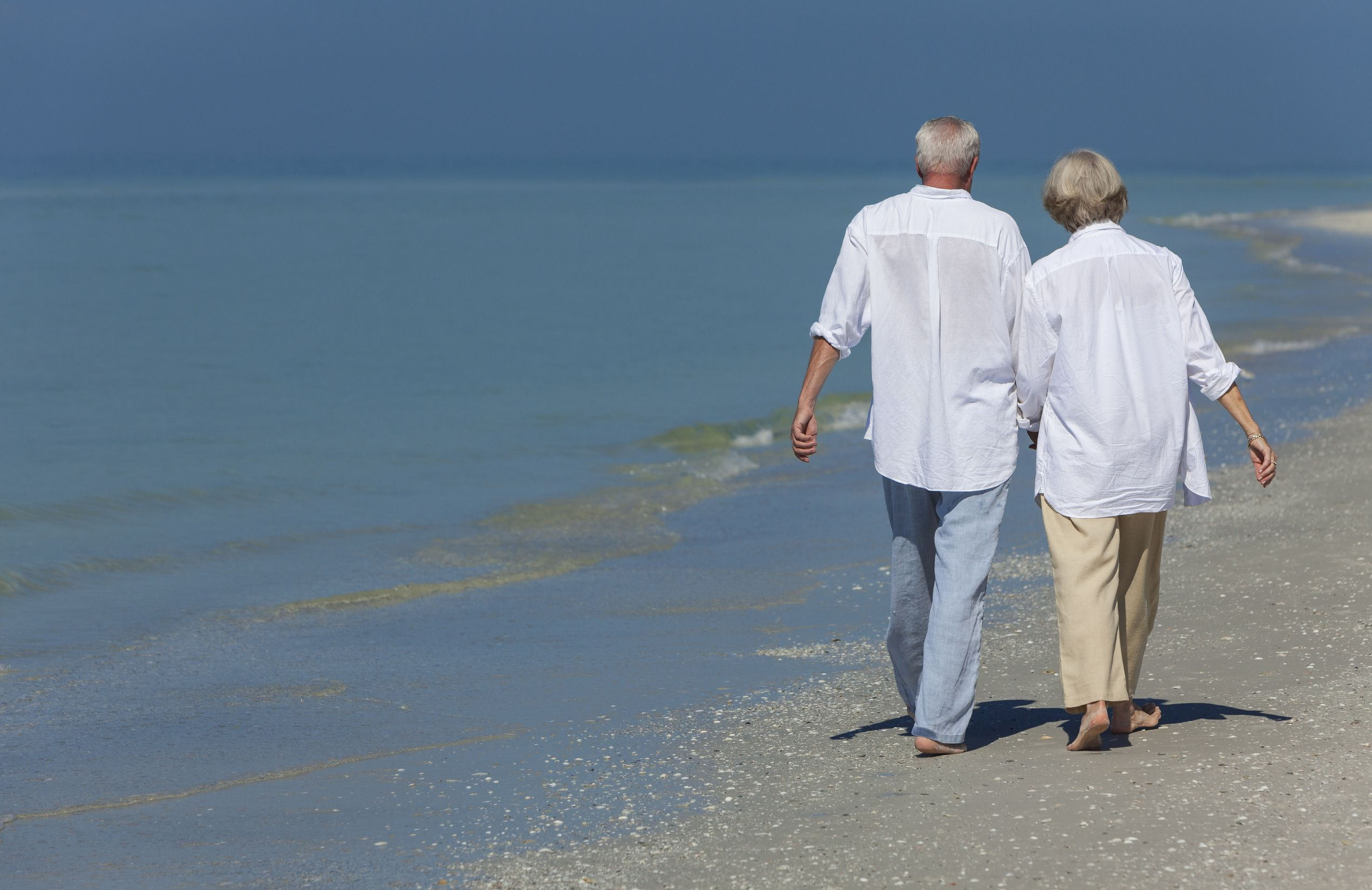 dmbaker130600007.jpg - rear view of happy senior man and woman couple walking and holding hands on a deserted tropical beach with bright clear blue sky