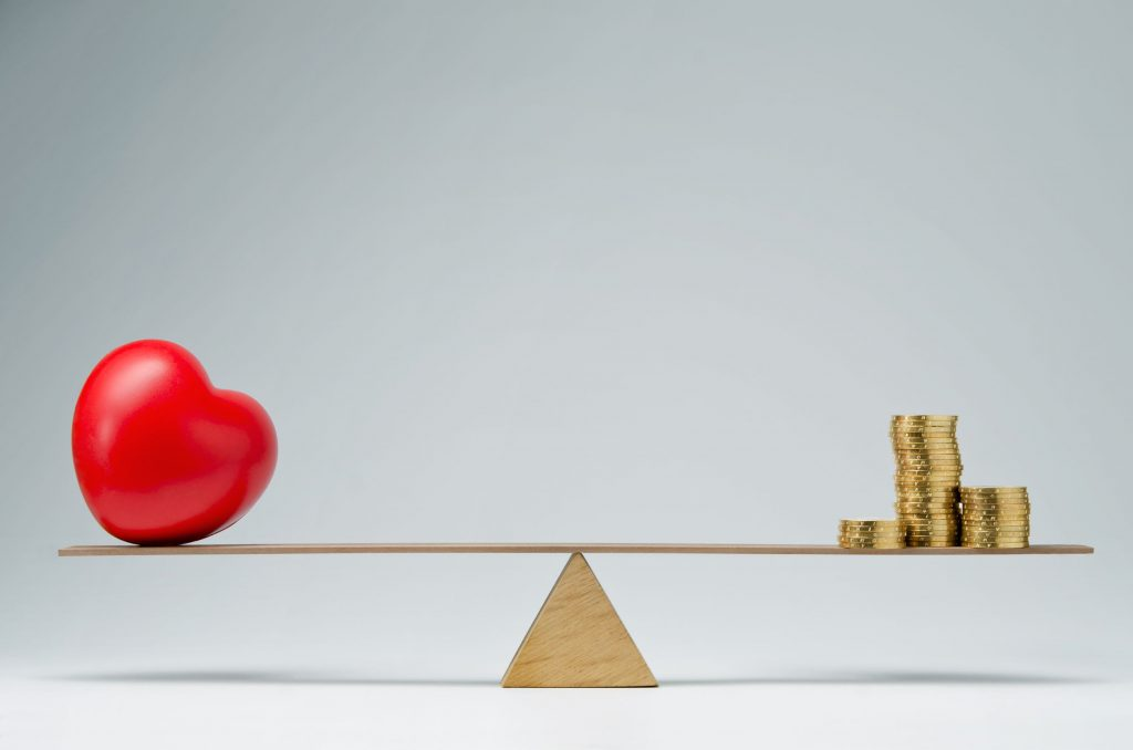 pogonici140600051.jpg - red heart shape and money coins stack balancing on a seesaw