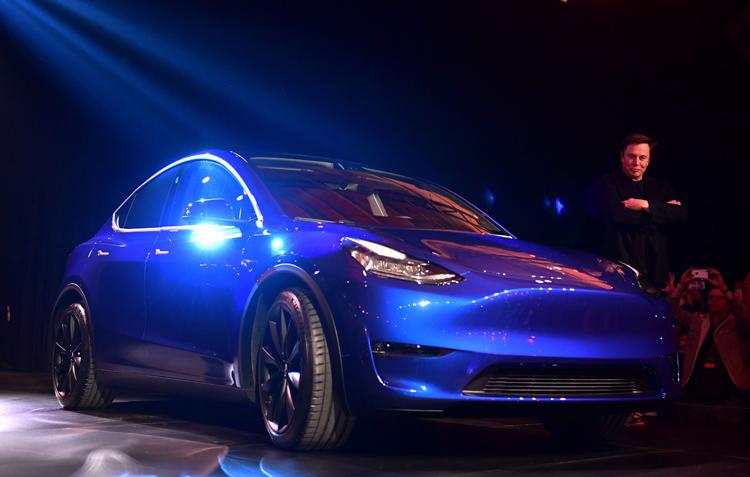 テスラの新型SUV「モデルY」とイーロン・マスクCEO(AFP=時事通信フォト)