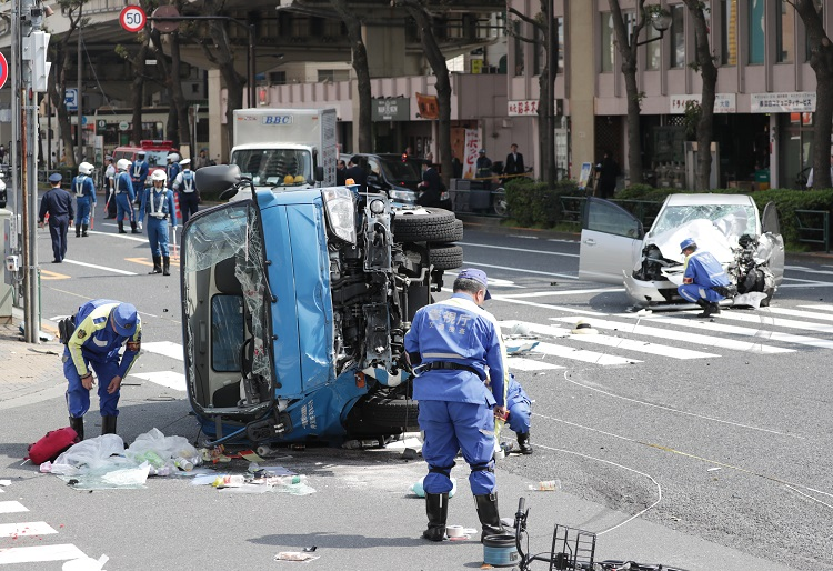 ごみ収集車と乗用車が衝突し、歩行者がはねられた事故現場を調べる警察官(時事通信フォト)