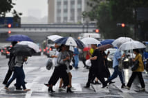People corss a street during a rainy afternoon in Tokyo on May 21, 2019. (Photo by Charly TRIBALLEAU / AFP)