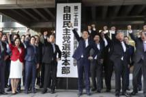 選挙本部の看板前で気勢を上げる安倍首相(共同通信社)