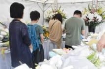 アニメ制作会社「京都アニメーション」近くに新たに設置された献花台で手を合わせる人々(時事通信フォト)