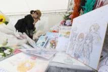 「京都アニメーション」第1スタジオ近くに設けられた献花台で手を合わせる女性(時事通信フォト)