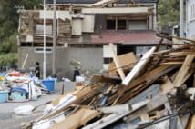 台風15号の影響で屋根や壁が壊れた家屋と積み上げられたがれき(千葉県鋸南町 共同通信社)