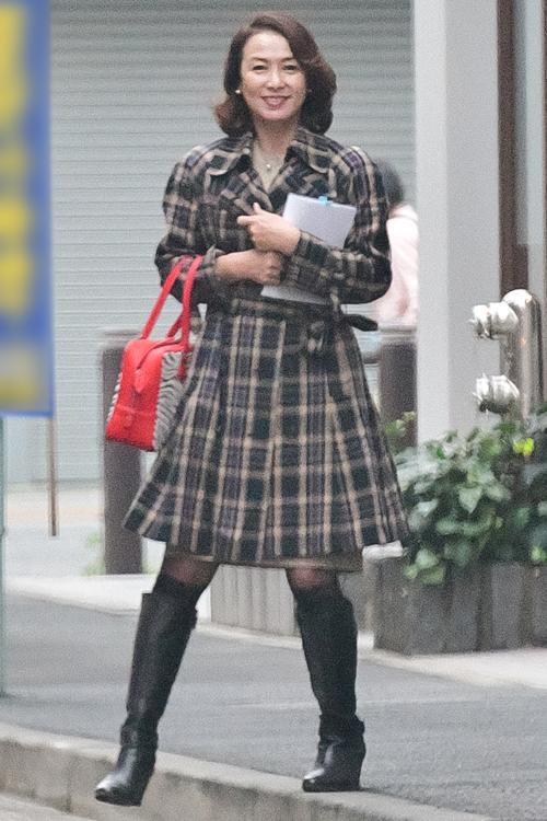 ワンピースのようなチェック柄コートにロングブーツ姿が若々しい