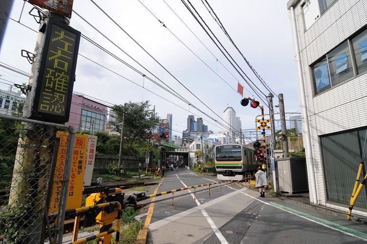 湘南新宿ラインの電車が通過中の青山街道踏切。前方に見えるのが山手線の高架、右手に見えるのが中央・総武線の高架。