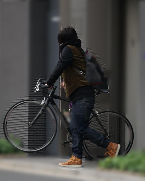 自転車を持ってマンションを出る秋山