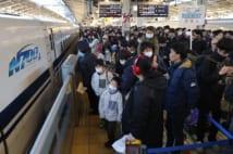 帰省する人たちで混雑するJR東京駅新幹線ホーム(時事通信フォト)