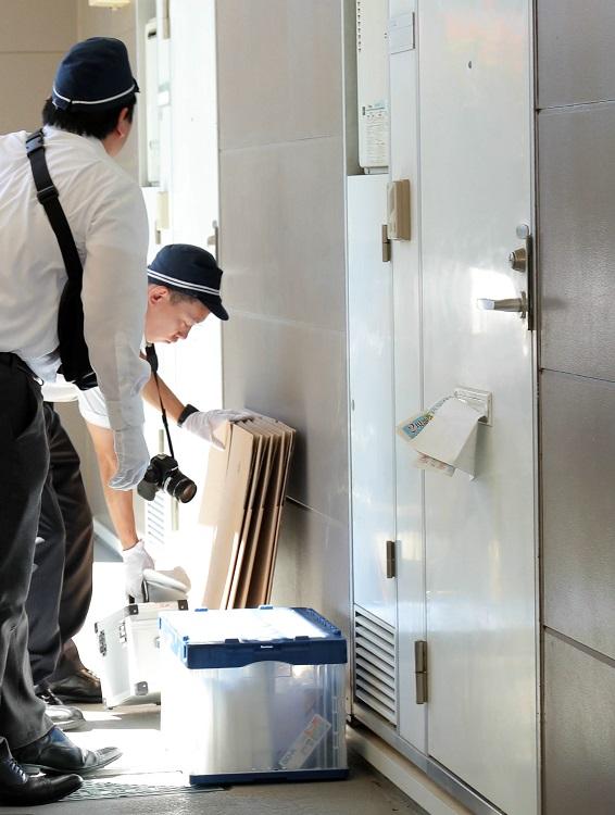 青葉真司容疑者宅に家宅捜索に入る京都府警の捜査員。青葉の自宅は普通のアパートの一室だった(時事通信フォト)