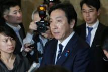 安倍晋三首相に辞表提出後、記者団の質問に答える菅原一秀経済産業相(中央)=25日、国会内