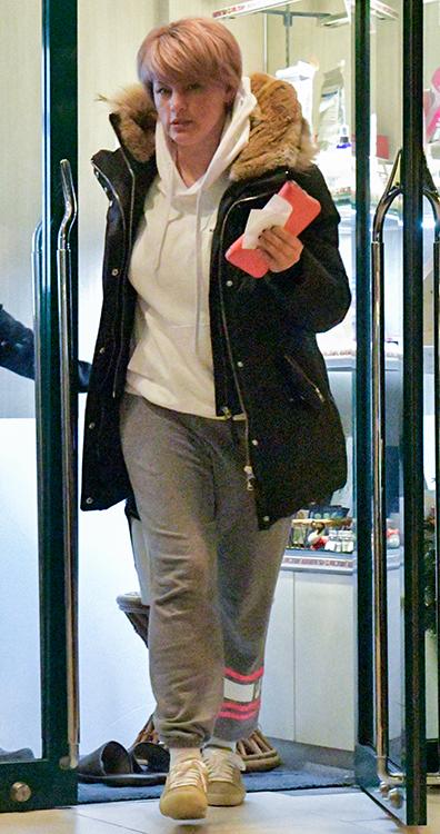 パーカーにジャケットを羽織って店の外へ出るアンナ