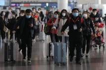 北京国際空港でマスクを着用して歩く乗客(EPA=時事通信フォト)