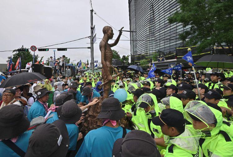 「徴用工像」をソウルの日本大使館に向けて動かす反日デモ参加者たち(AFP=時事)