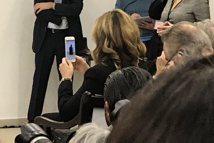 会見中、夫の姿をスマホで撮影するキャロル夫人