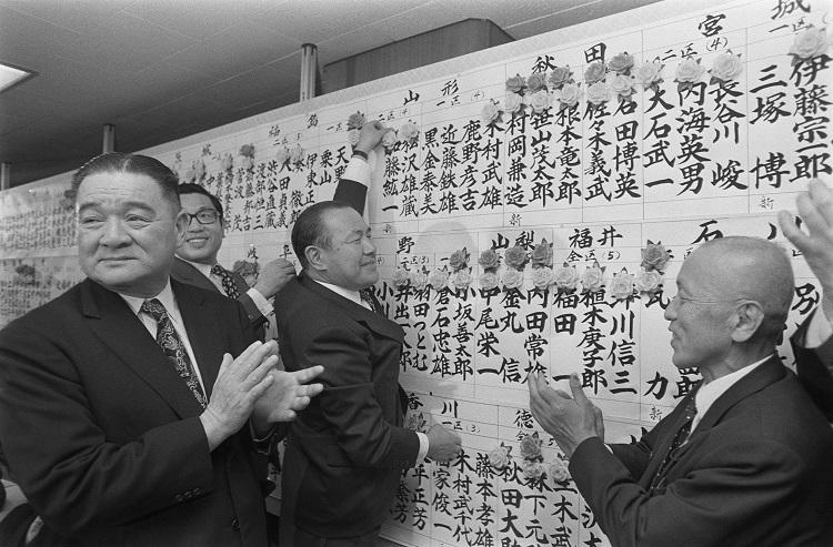 1972年総選挙で当選者の名前の上にバラの花を着ける自民党の田中角栄総裁(中央)(時事通信フォト)