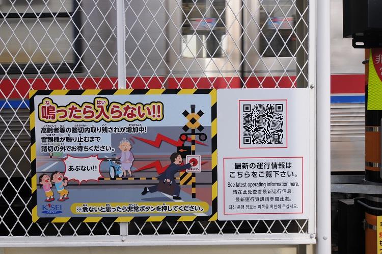 京成本八幡駅に隣接した踏切に設置されたQRコード付き看板