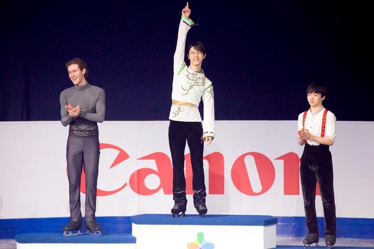 2位のジェイソン・ブラウン選手と3位の鍵山優真選手とハグで健闘をたたえ合った後、勢いよく1位の表彰台にジャンプ(写真/アフロ)