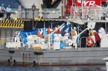 クルーズ船内で発見された感染者を搬送する救急隊員ら(時事通信フォト)