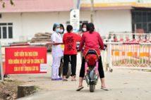 2月13日にいち早く隔離措置がとられたソンロイ村の検問所で、食料や日用品を外部から受け取る村民。村は3月4日に解放された(2月29日撮影)