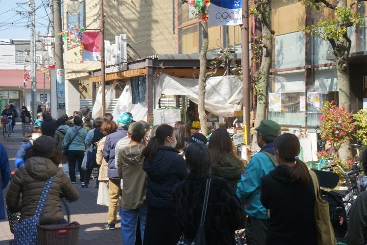 3月末、開店前のスーパーに並ぶ買いだめ目的と思われる人々(時事通信フォト)