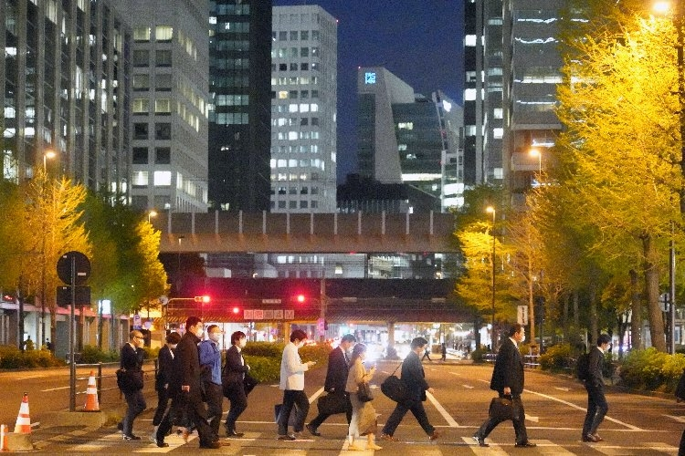 マスク姿で帰途につく東京・大手町のサラリーマン(時事通信フォト)