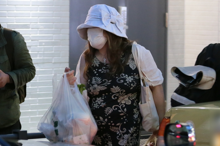 買い物袋を提げて帰宅する小室佳代さん
