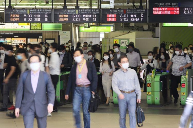 緊急事態宣言解除後、初めての朝を迎えた新宿駅の人波(時事通信フォト)