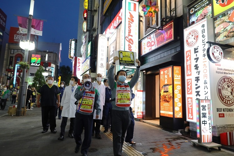 歌舞伎町では都職員らが感染防止呼びかけの巡回をおこなっている(時事通信フォト)