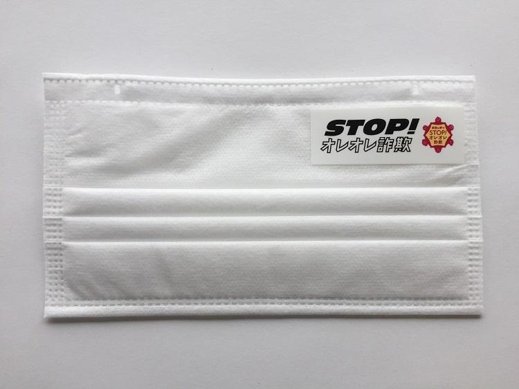 特殊詐欺被害の防止を訴えるステッカーを貼ったマスク(警察庁提供、時事通信フォト)