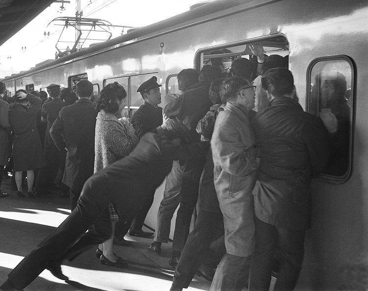 ぎゅう詰めの車内に通勤客を押し込む国鉄職員。1967年新宿駅(時事通信フォト)
