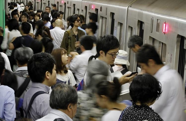 午前8時台の通勤ラッシュで混む都営大江戸線の新宿西口駅のホーム(時事通信フォト)