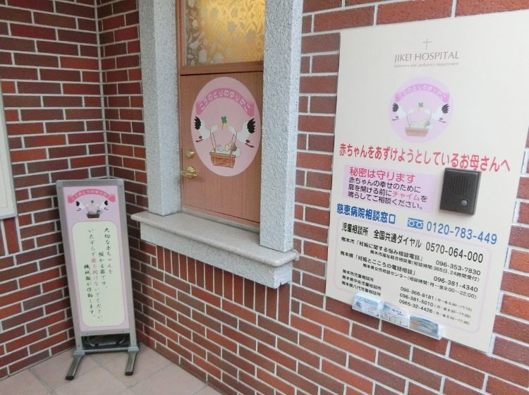 中央に見える扉の右側には、インターホンとともに母親へのメッセージが書かれている(時事通信フォト)