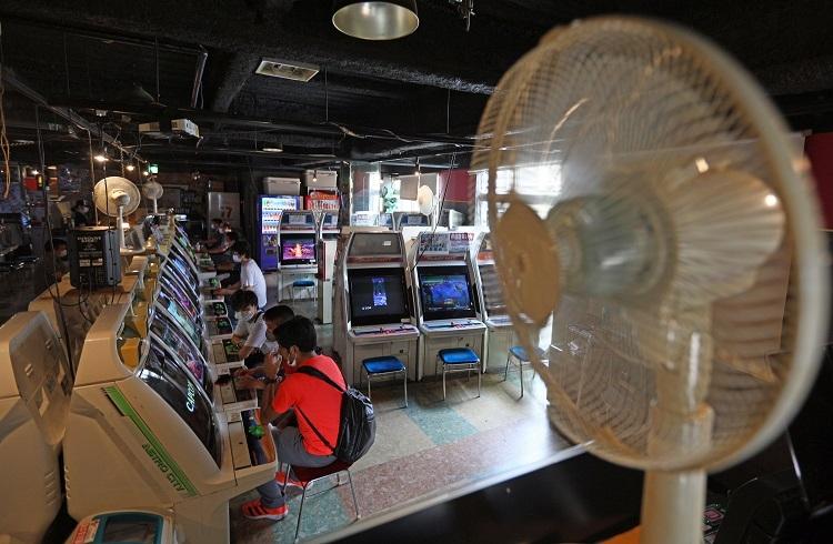 換気対策のため扇風機を置き窓が開けて営業再開したゲームセンター(時事通信フォト)
