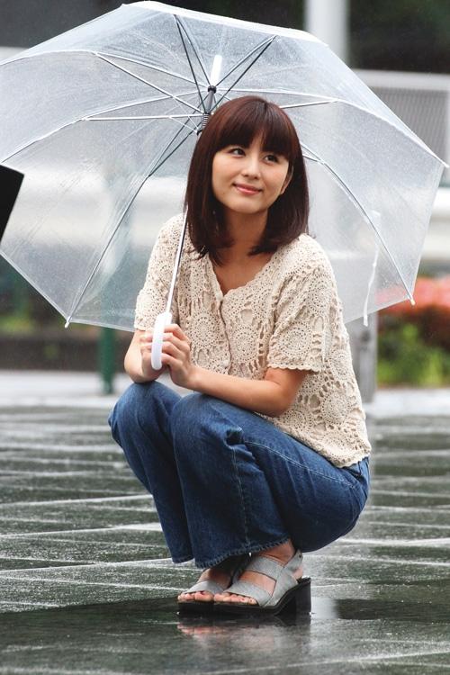 傘をさしてしゃがみ、微笑む宇賀なつみ