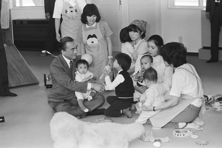 1983年「国際救援センター」の落成・開所式典に出席、ベトナム難民の幼児を抱く中曽根康弘首相(時事通信フォト)