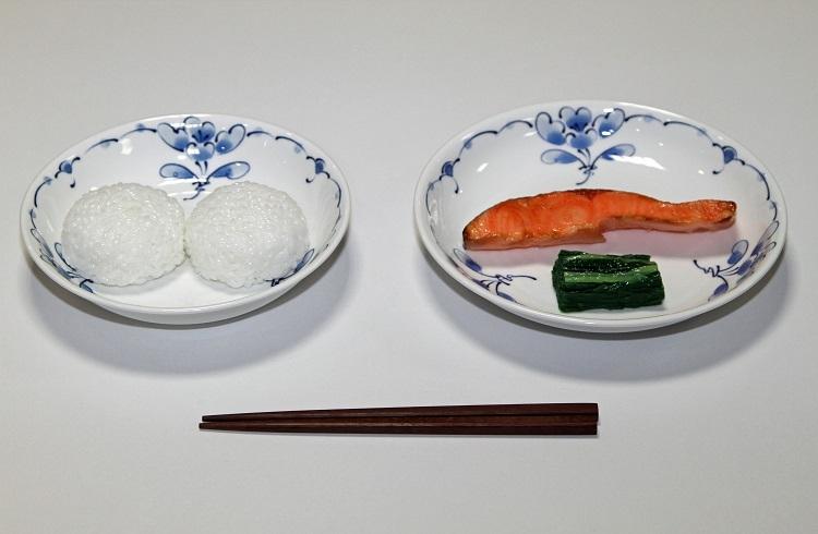 学校給食は長らく子供たちの栄養を支えてきた。明治22年の給食献立。おにぎり、塩鮭、菜の漬物。学校給食歴史館の展示サンプル(時事通信フォト)