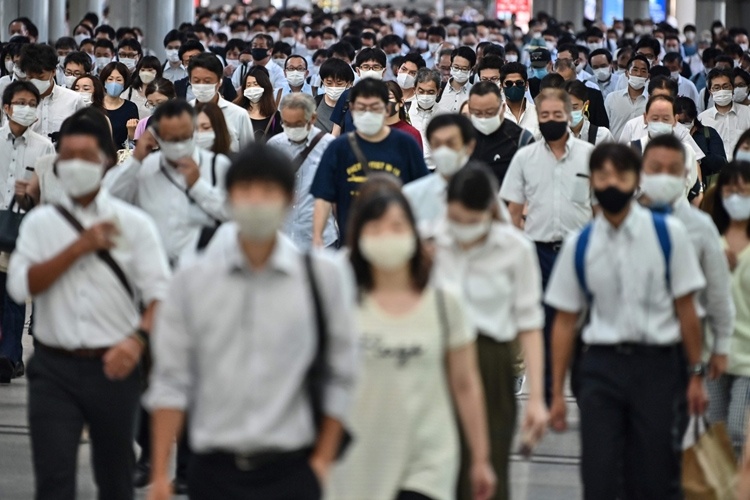 マスク装着が欠かせなくなった朝の通勤風景(AFP=時事通信フォト)