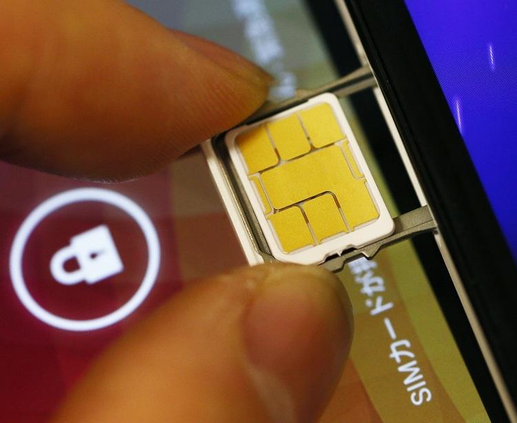 利用者の固有IDが記録されるSIMカード。これを挿すことでスマホなどが使用可能になる(時事通信フォト)
