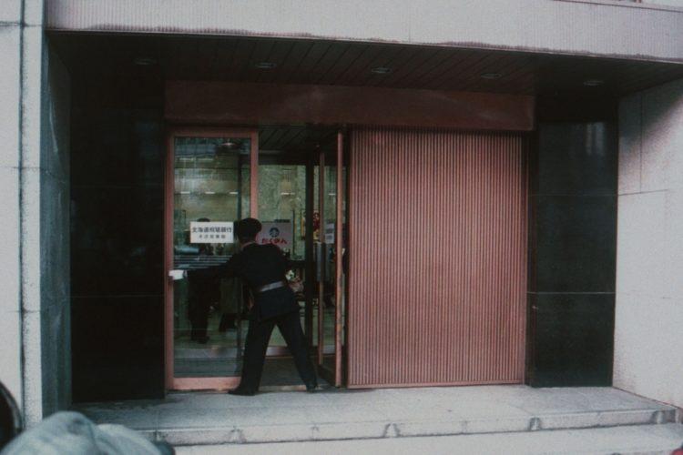 最後の営業を終え、シャッターを閉める北海道拓殖銀行本店(1998年11月/時事通信フォト)