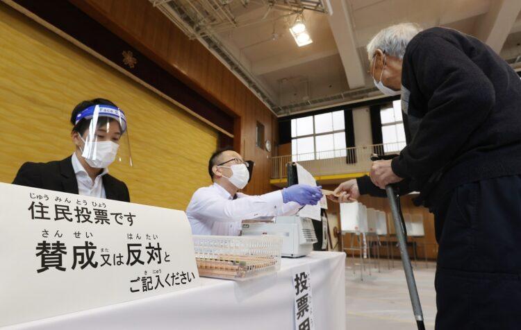 「大阪都構想」の是非を問う住民投票の投票用紙を受け取る有権者(右)(時事通信フォト)