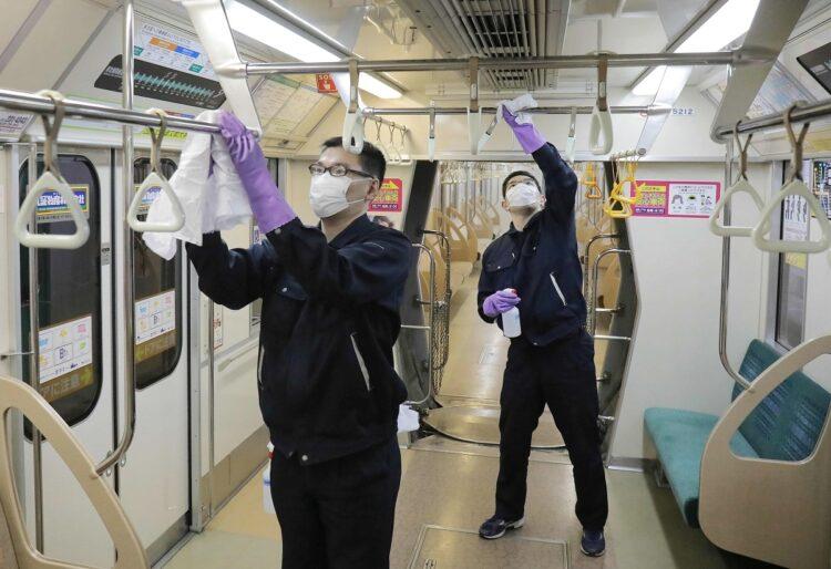 3月の札幌市、アルコール消毒液で地下鉄車両のつり革などを拭く清掃業者(時事通信フォト)