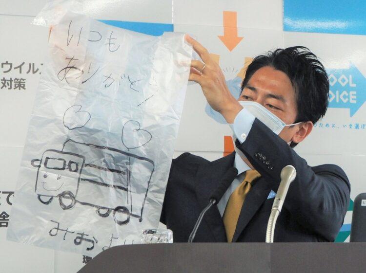 ごみ収集作業員へのメッセージと絵が描かれたごみ袋を紹介する小泉進次郎環境相。エッセンシャルワーカーへ感謝をという気運が高まっていた2020年4月(時事通信フォト)