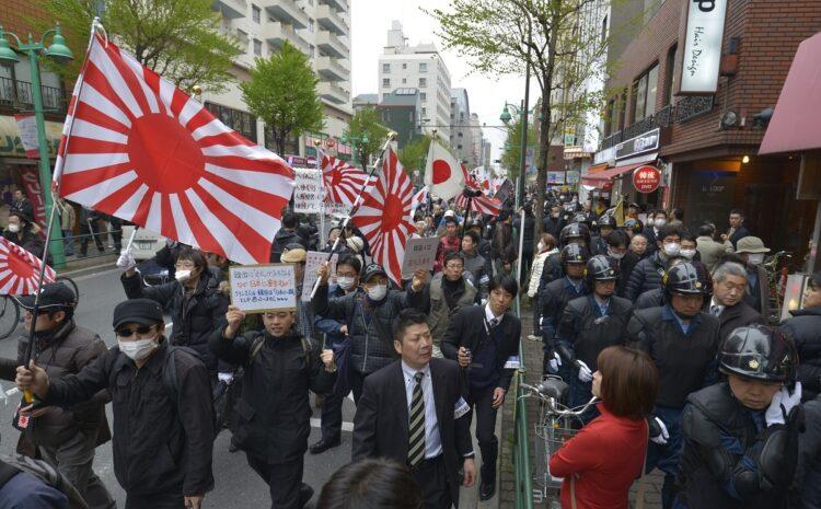 日章旗や旭日旗を振りながら大久保通りを行進するデモ参加者。韓国系の商店や料理店が集まる新宿・新大久保で在日外国人排外などを叫ぶデモが行われた。写真は2013年3月(時事通信フォト)