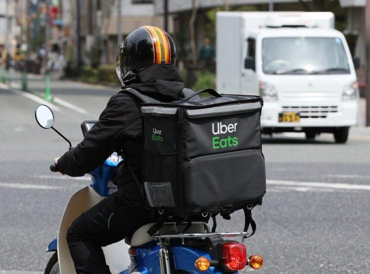 街中を走る「ウーバーイーツ」の配達員。ほとんどの配達員が自転車もしくは原付バイクで配達している(イメージ、時事通信フォト)
