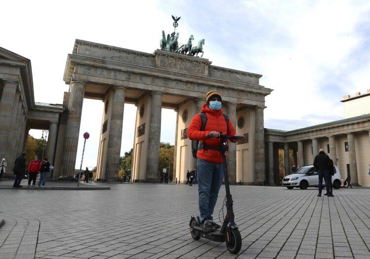 ドイツ・ベルリンのブランデンブルク門前を電動キックスケーターで移動する男性(EPA=時事)