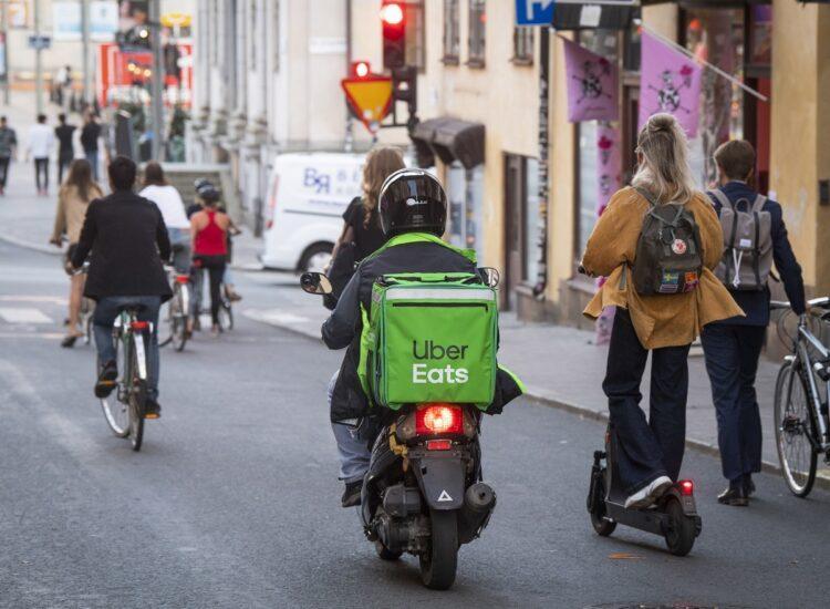 フードデリバリー中のバイク、自転車、電動キックスケーターが併走するスウェーデン・ストックホルム(EPA=時事)